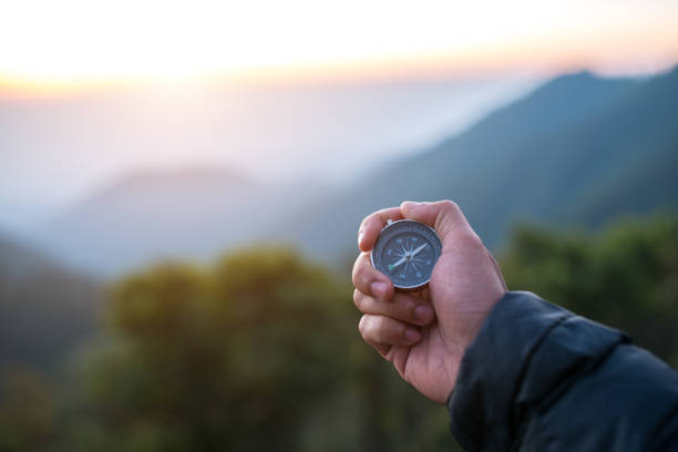 Male hand with compass Travel concept,Male hand with compass on mountains background compass stock pictures, royalty-free photos & images