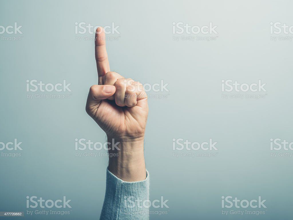 Male hand with finger pointing up stock photo