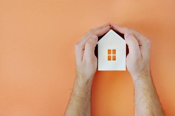 Male hand with model house. Flat lay style stock photo