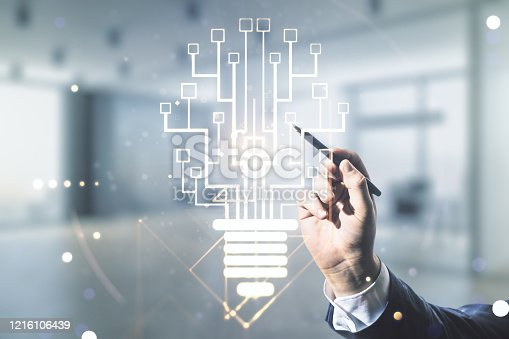 istock Male hand with pen draws virtual creative light bulb with chip hologram on blurred office background, artificial Intelligence and neural networks concept. Multiexposure 1216106439