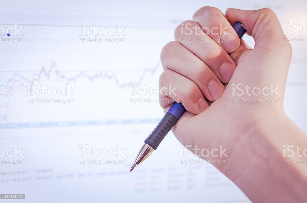 Male hand with pen watching stock exchange royalty-free stock photo