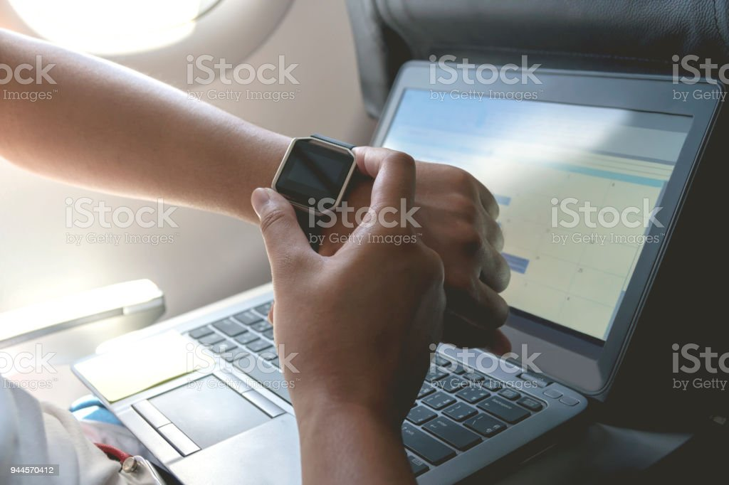 Male hand with smart watch on wrist. Planning agenda and schedule using calendar event planner. Calender planner of travel on airplane. stock photo