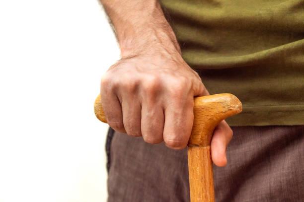 Male hand with walking stick holding praying beads stock photo
