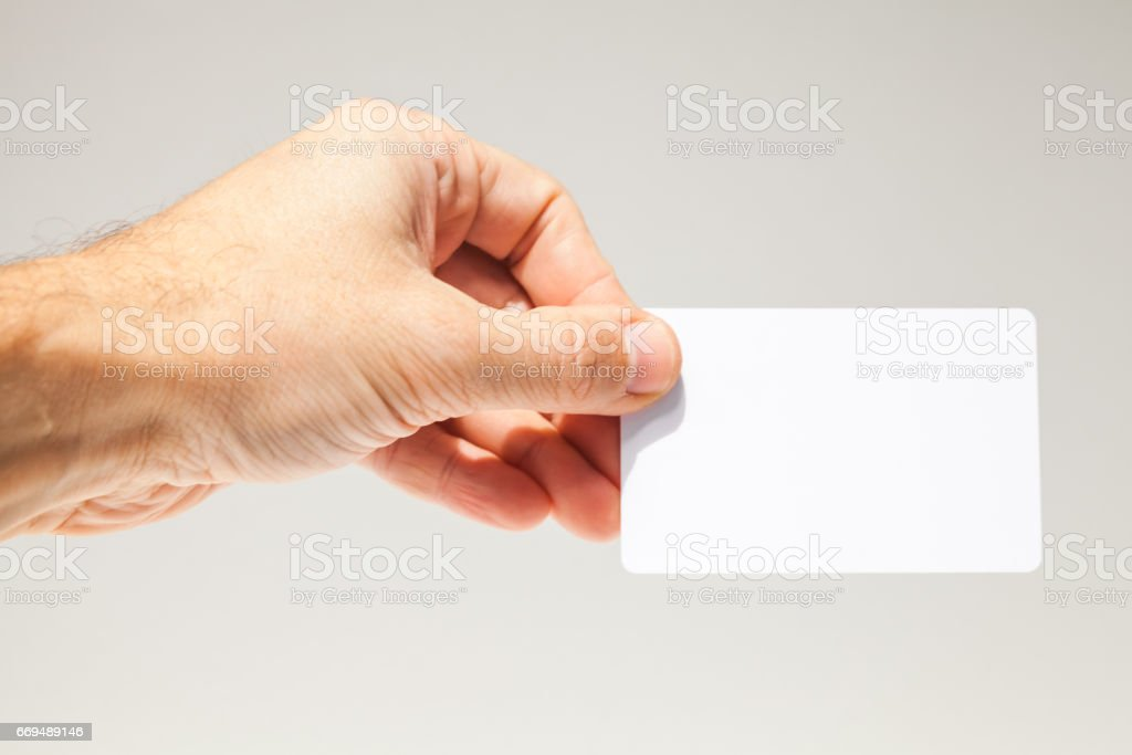 Male hand with white empty card over gray stock photo