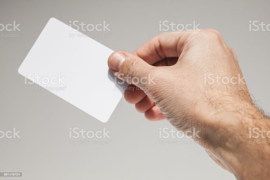 Male hand with white empty card over gray wall stock photo