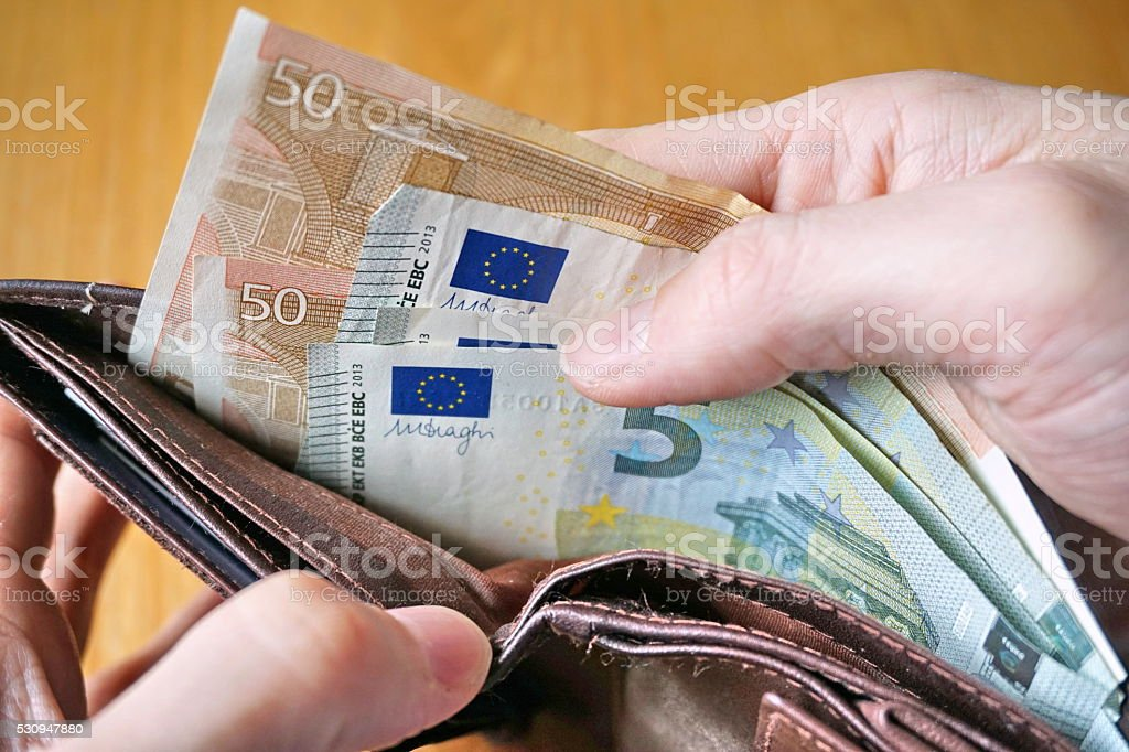 Male hand withdrawing European currency (EUR, Euro) from wallet stock photo