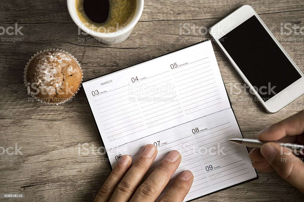 male hand writing at planning notebook stock photo