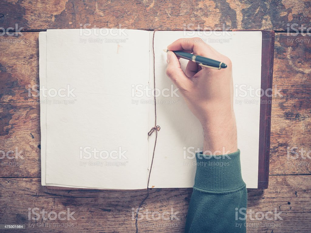 Male hand writing in notepad stock photo
