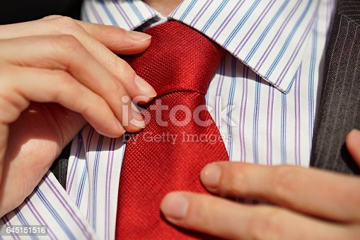 973213156 istock photo Male hands adjusting a red tie around a neck 645151516