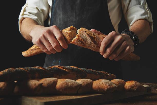 Männlichen Händen brechen das baguette – Foto