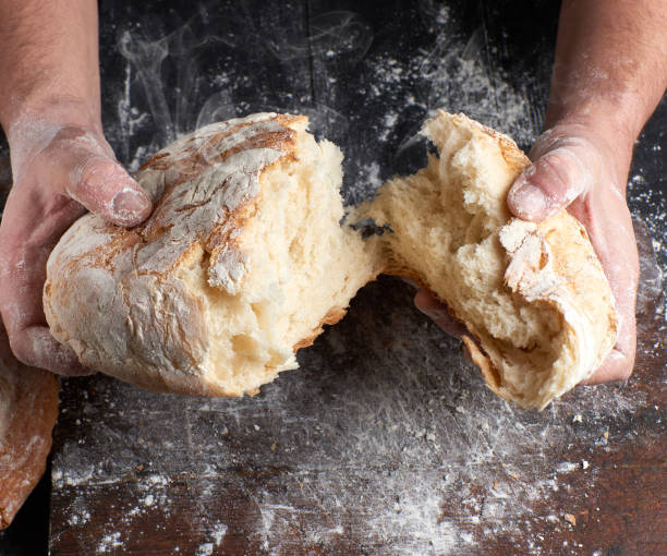 male hands breaking open baked bread in half male hands breaking open baked bread in half over black wooden table bread stock pictures, royalty-free photos & images