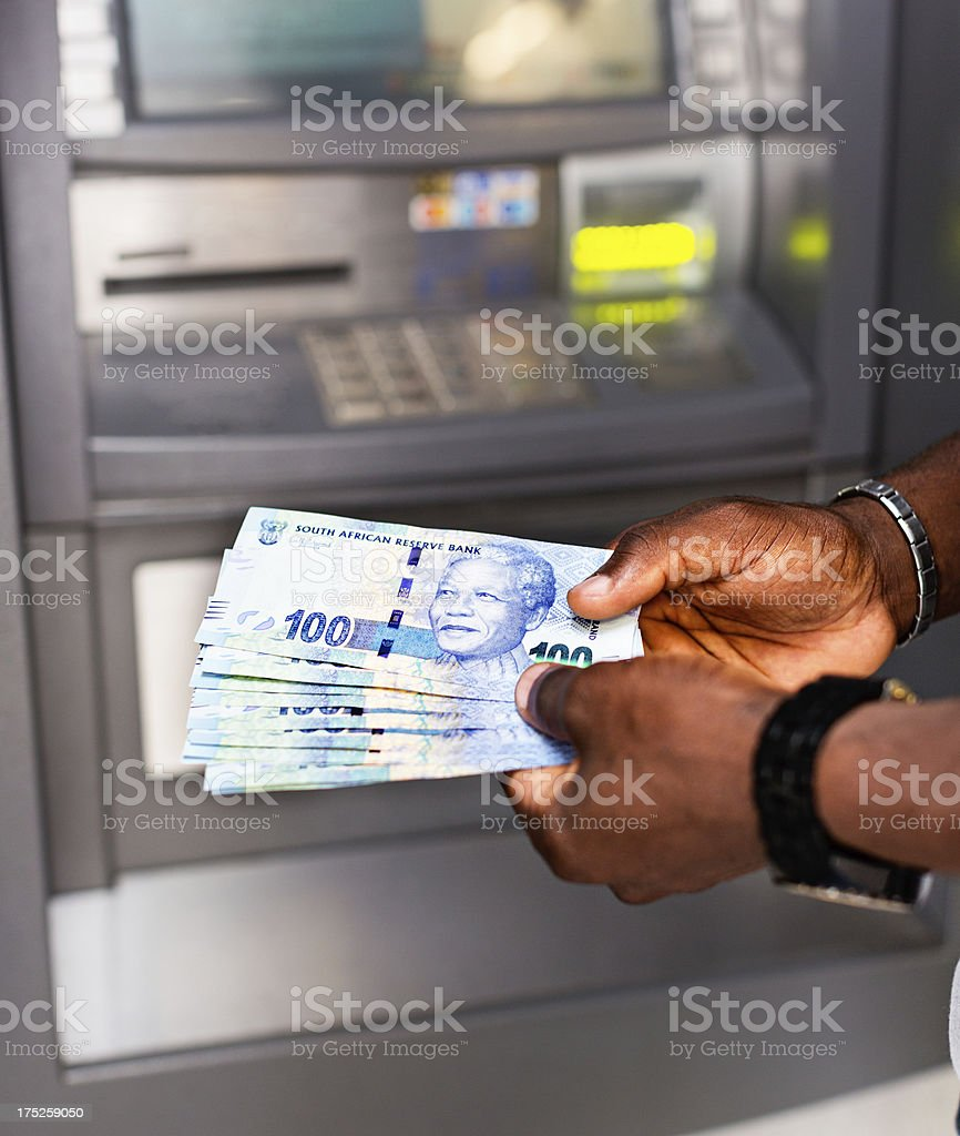 Male hands by ATM with sheaf of Hundred Rand banknotes stock photo
