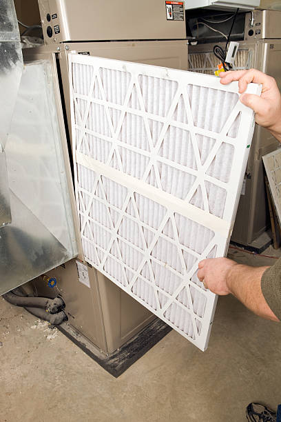 Male Hands Change Large Pleated Furnace Air Filter  lighting technique stock pictures, royalty-free photos & images