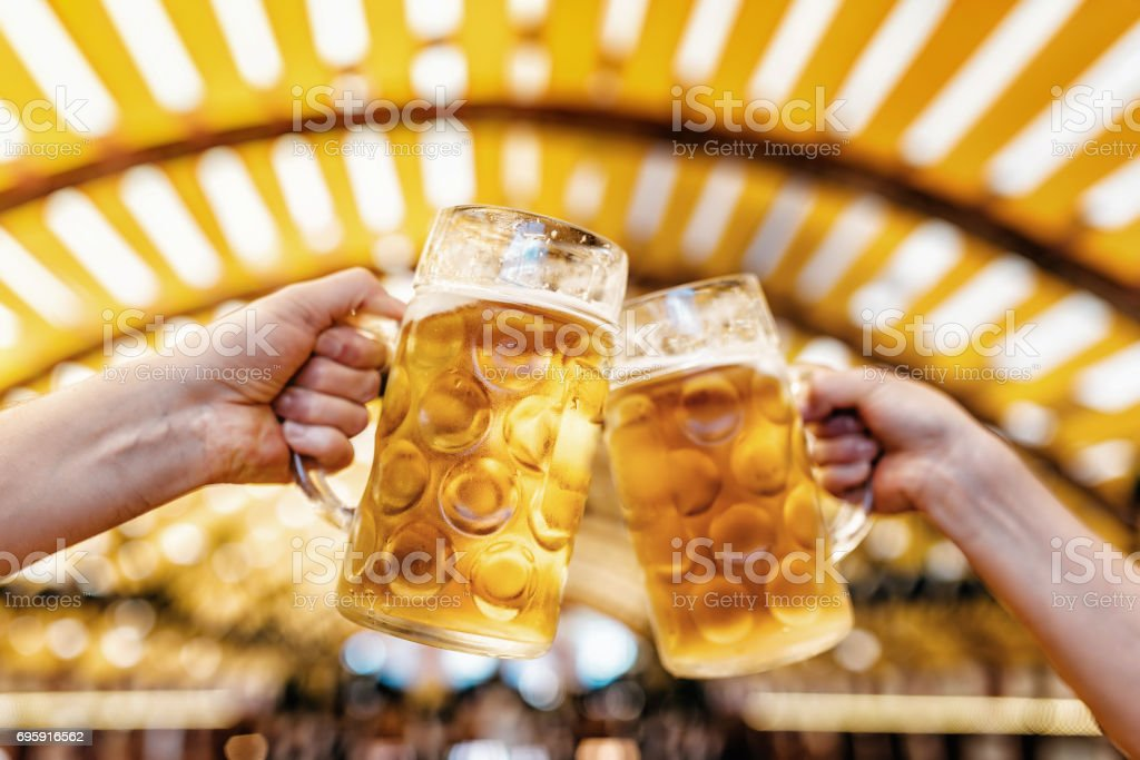 male hands clinking mass-beer glasses at oktoberfest in munich stock photo