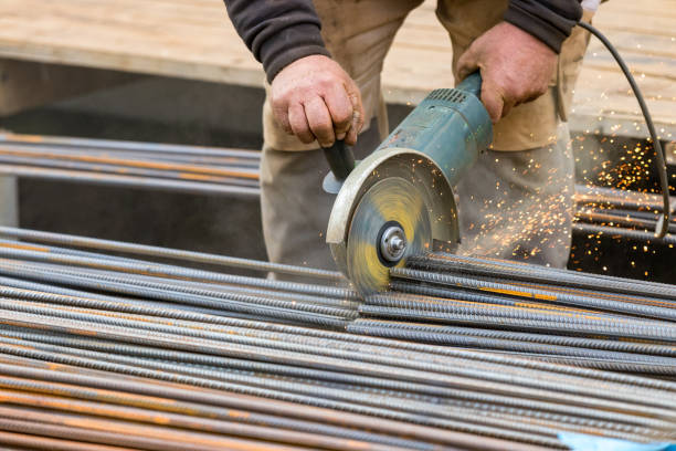Male hands cutting steel bars with a circular electric grinder. stock photo