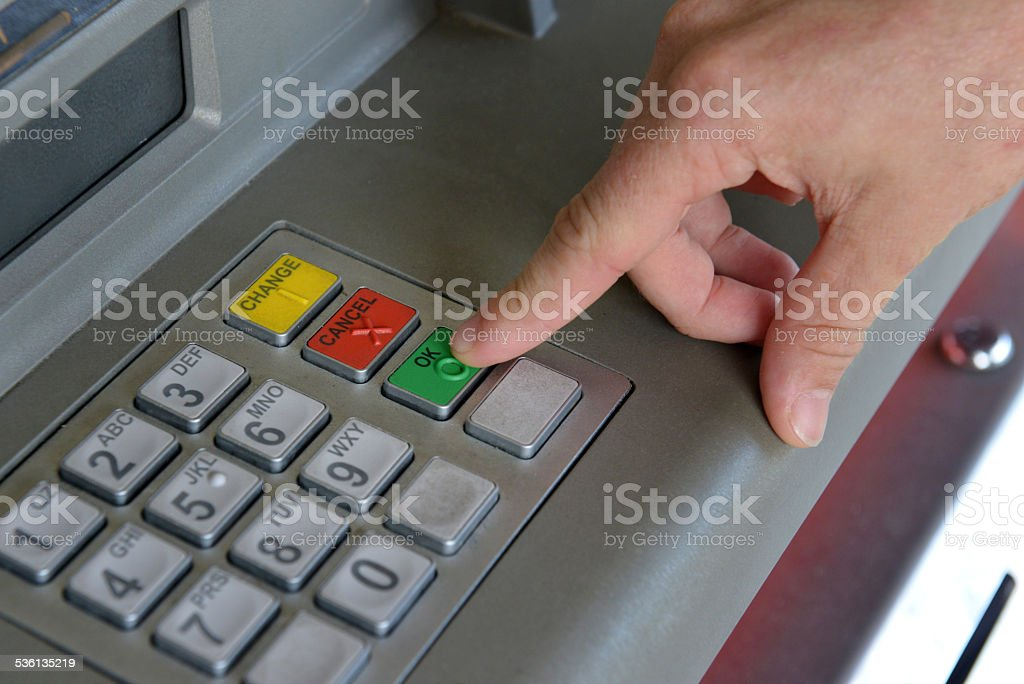 Male hands doing banking at an ATM stock photo
