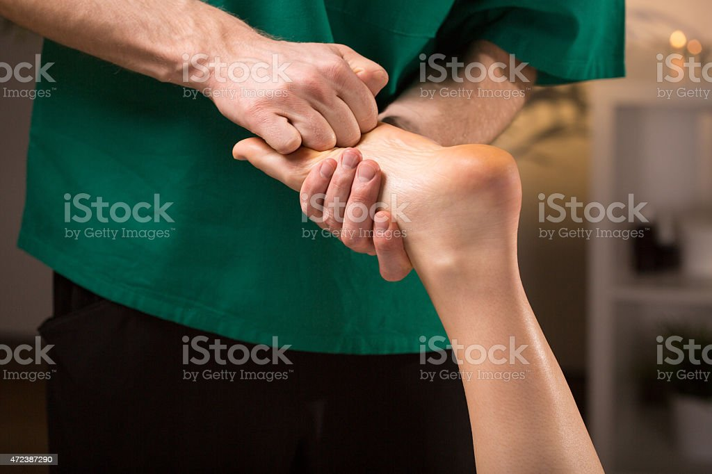 Male hands doing foot massage stock photo