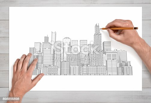 821915804 istock photo Male hands drawing a city crape with many skyscrapers with a pencil on a white paper in close view 898856898