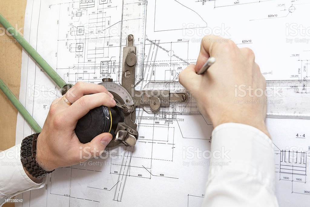 Male hands drawing on blueprint by pencil stock photo
