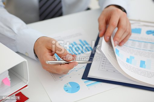 istock Male hands hold documents with financial statistics 938614778
