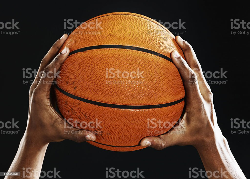 Male hands hold up a basketball against black stock photo