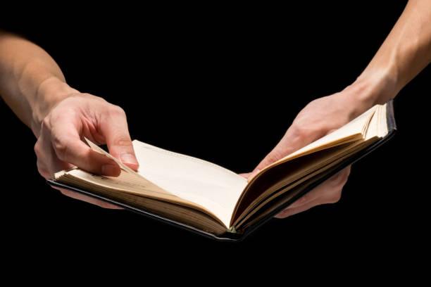 männlichen händen mit einer leeren arbeitsmappe auf einem schwarzen hintergrund. - lesen arbeitsblätter stock-fotos und bilder