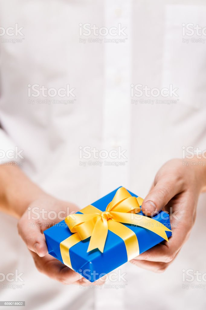 Male hands holding a blue gift box with ribbon. royalty-free stock photo