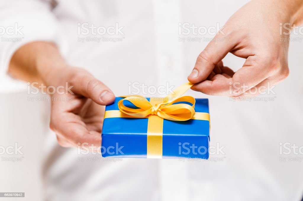 Male hands holding a blue gift box with ribbon. stock photo