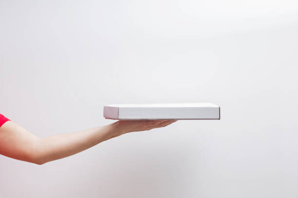 Male hands holding a box with pizza against the white wall with copy space. stock photo