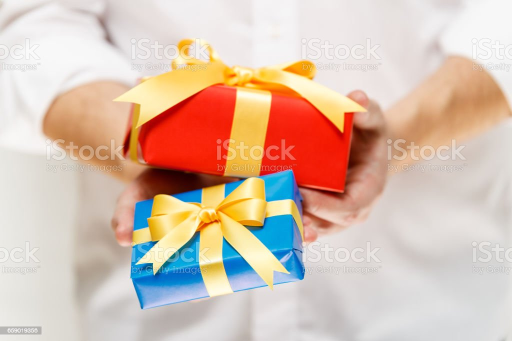 Male hands holding a gift boxes with ribbon. royalty-free stock photo