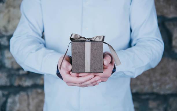 männliche hände halten ein geschenk - verlobung was schenken stock-fotos und bilder