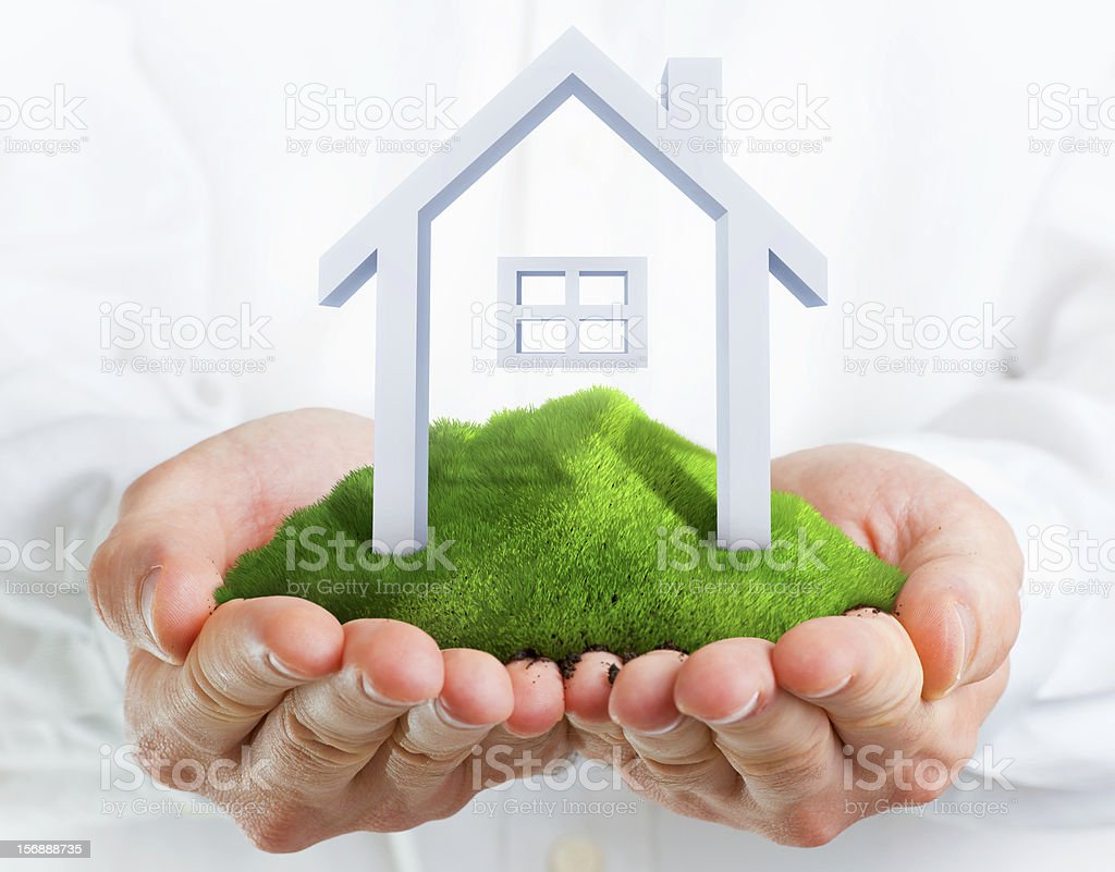 Male hands holding a green hill with small house stock photo