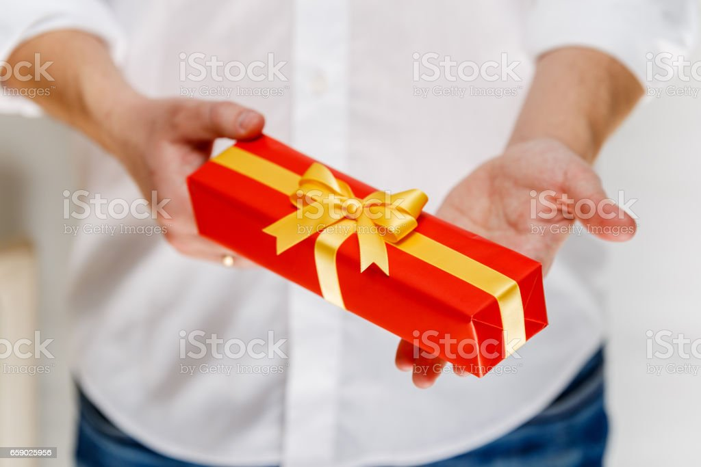Male hands holding a red gift box with ribbon. royalty-free stock photo