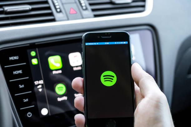 手持智慧手機的男性手, 連接到汽車運行流行音樂流服務的電腦 - music 個照片及圖片檔