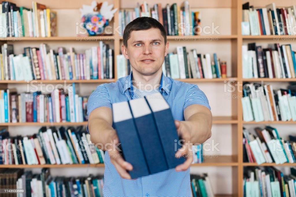 Male hands holding a stack of books. Man holds out a stack of books royalty-free stock photo