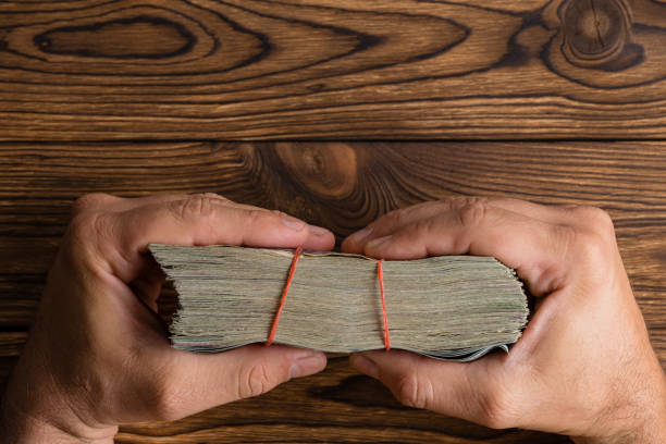 Male hands holding a thick wad of money stock photo
