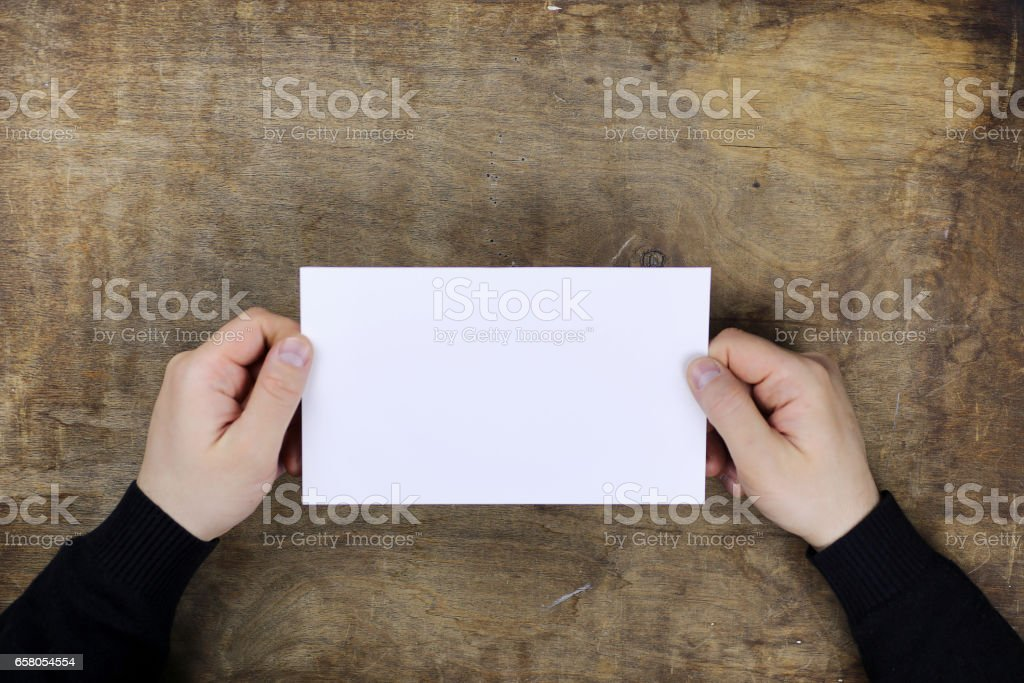 male hands holding a white blank sheet of paper stock photo