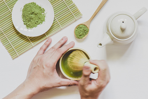 male hands holding cup of green matcha tea on white wooden background
