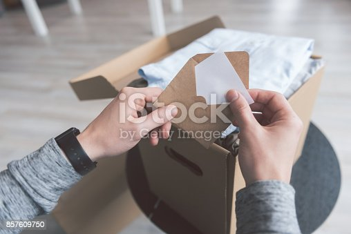 istock Male hands holding envelope with message 857609750
