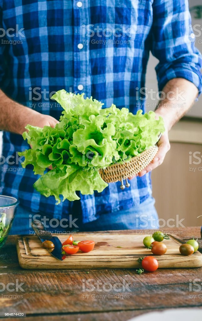 Male hands holding fresh lettuce leaf at home in the kitchen sunny evening. Healthy food concept royalty-free stock photo