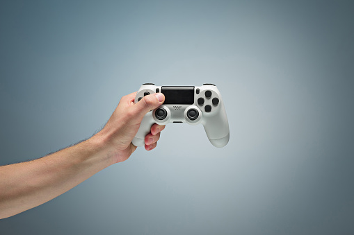 istock Male Hands Holding Gamepad 907819800