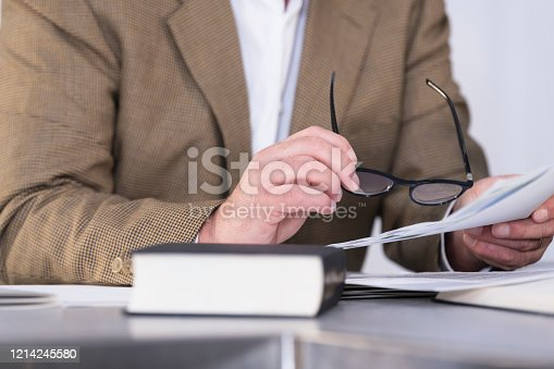 Close-up of a man right hand holding glasses while holding a document with his right hand with an out of focus book at the front. Workplace and business concept.