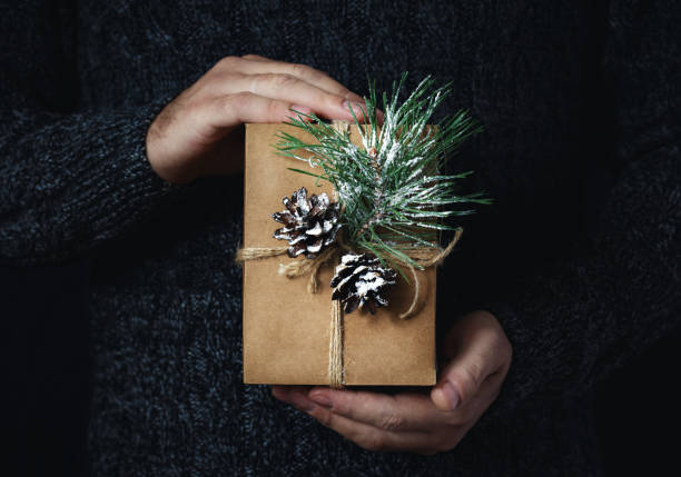 männliche hände halten hausgemachte weihnachten geschenk dunklen hintergrund weihnachten hintergrund - bastelkarton stock-fotos und bilder