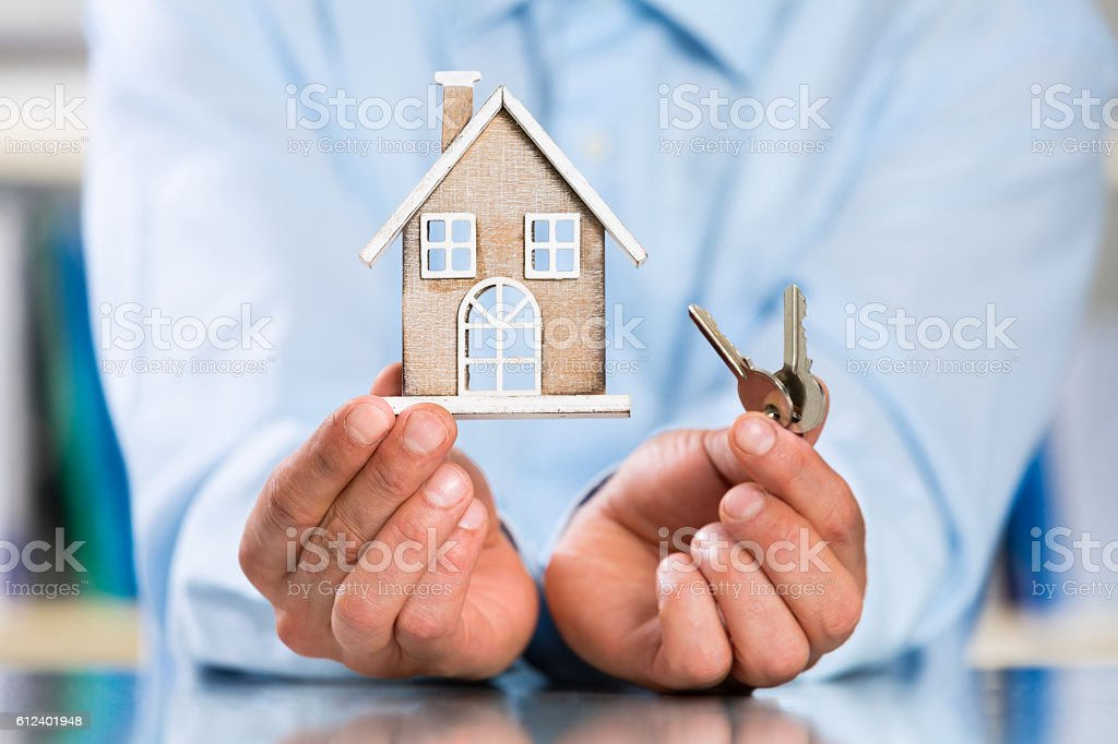 Male Hands holding Miniature House and House Key stock photo