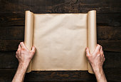 istock Male hands holding old paper scroll 1139094176