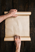 istock Male hands holding old paper scroll 1139094183