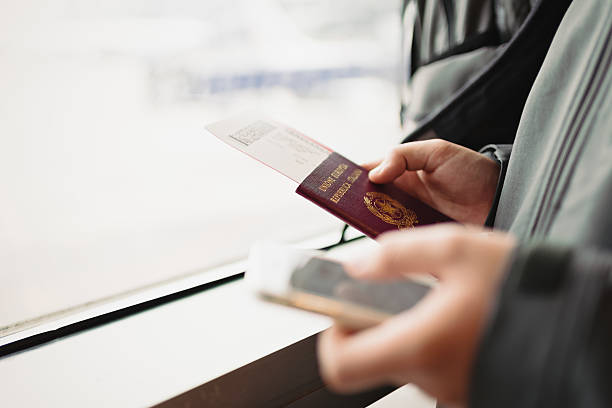 Male hands holding passport, ticket for plane and smart phone stock photo