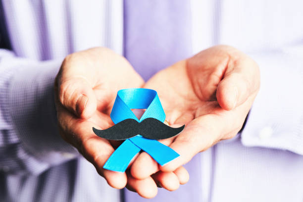 Male hands holding prostate cancer awareness ribbon with mustache Male hands holding prostate cancer awareness ribbon with mustache prostate gland stock pictures, royalty-free photos & images