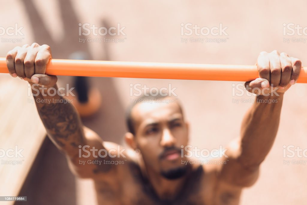 Male hands holding pull ups bar outdoors stock photo