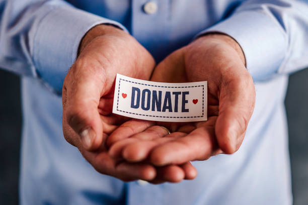 Male hands holding sign reading donate stock photo